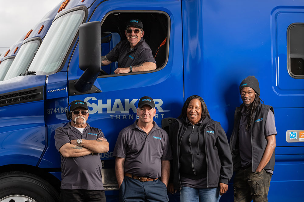 group of employees with one in cab of truck and rest standing in front