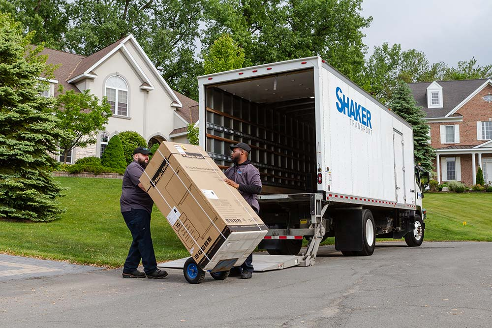 2 men unloading refrigerator out of deliver truck