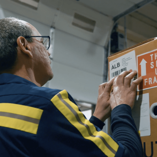 Man in warehouse writing on a box